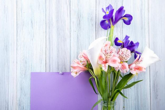 Vue latérale d'un bouquet de fleurs d'alstroemeria de couleur rose et de fleurs d'iris violet foncé dans une bouteille en verre avec une feuille de papier violette attachée sur un fond en bois gris