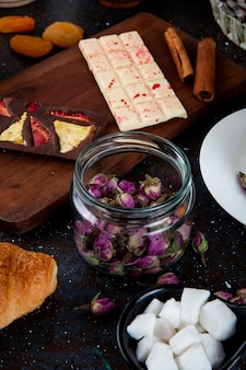 Vue latérale des boutons de rose secs dans un bocal en verre et chocolat noir et blanc sur une planche à découper en bois avec des bâtons de cannelle sur rustique