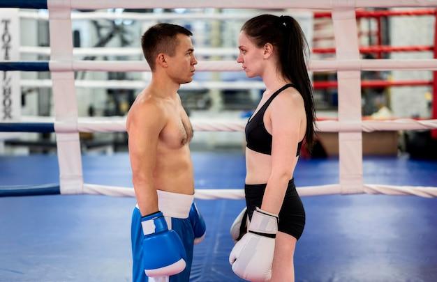 Vue latérale des boxeurs masculins et féminins dans le ring