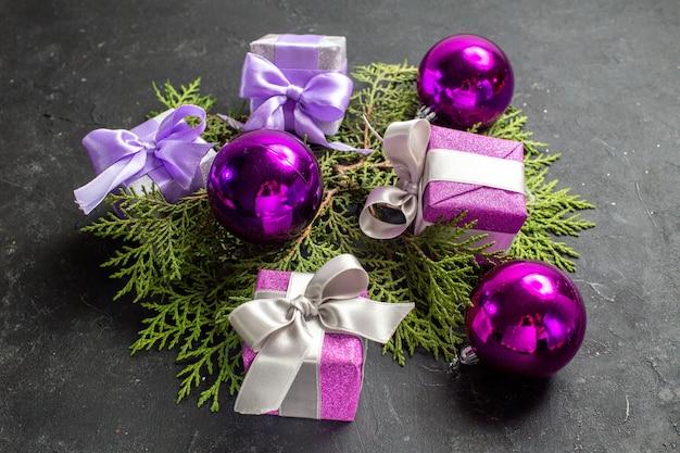 Vue latérale des cadeaux colorés et accessoires de décoration sur fond sombre