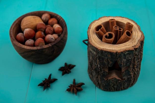 Vue latérale de la cannelle dans un bol d'arbre et bol de noix sur fond bleu