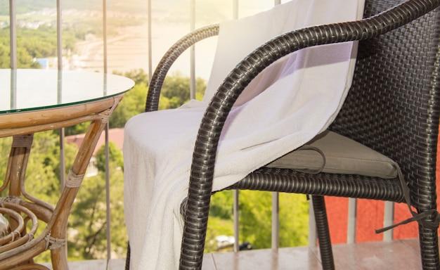 Vue latérale d'une chaise en osier avec une serviette éponge blanche pour spa et une table ronde en verre, intérieur du balcon, extérieur