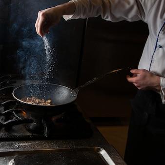 Vue latérale champignon frire avec sel et feu et main humaine dans la casserole