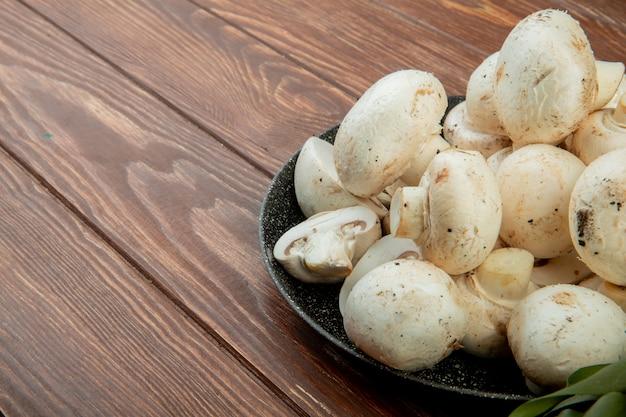 Vue latérale des champignons blancs frais isolés sur bois rustique avec espace copie