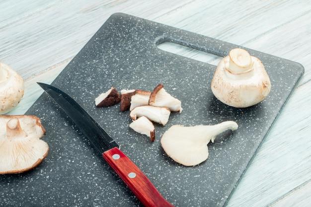 Vue latérale de champignons frais entiers et tranchés avec un couteau de cuisine sur une planche à découper noire sur une table rustique