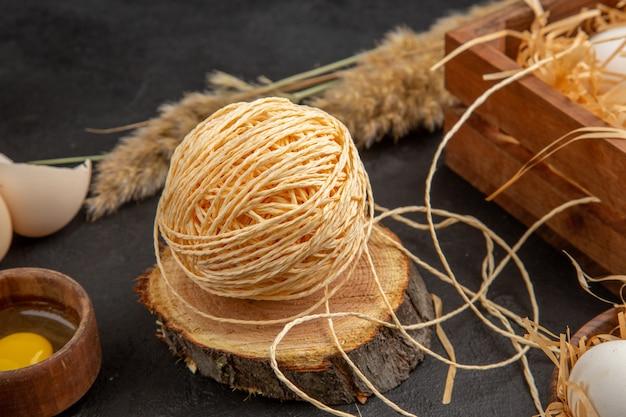 Vue latérale des chaws jaunes dans une boîte en bois, des pointes de corde d'oeufs cuillères sur fond noir