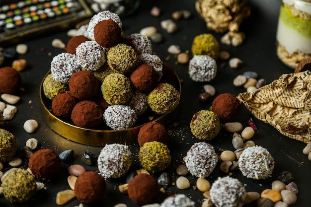 Vue latérale des chocolats colorés avec des cailloux sur table noire