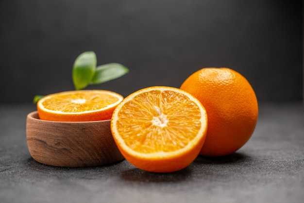 Vue latérale des citrons frais entiers et coupés avec des feuilles sur fond sombre