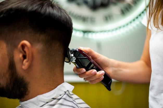 Vue latérale d'un client se faisant couper les cheveux