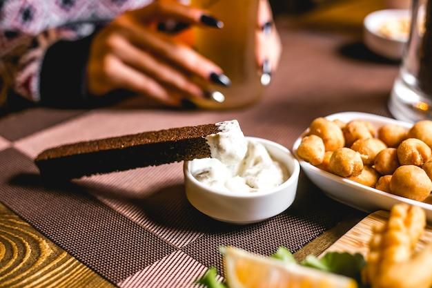 Vue latérale des collations de bière crouton de pain brun avec sauce et petits pois frits
