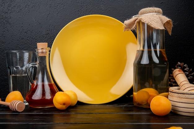 Vue latérale de la compote d'abricot et du sirop de pêche aux abricots et au broyeur d'ail sur une surface en bois et fond noir
