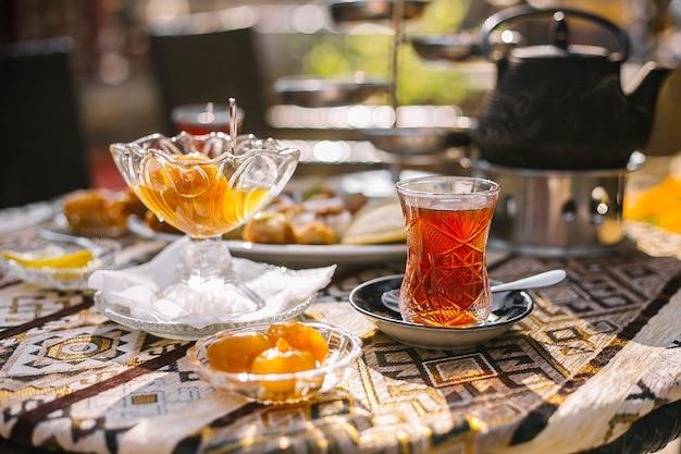Vue latérale de la confiture de figues maison dans une soucoupe en verre et un vase servi avec du thé sur la table