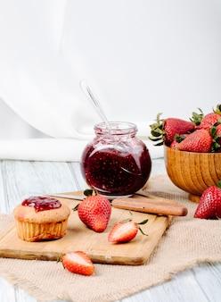 Vue latérale de la confiture de fraises avec cupcake fraise fraîche dans un bol en bois et couteau sur fond blanc