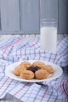 Vue latérale des cookies sur une plaque blanche servie avec un verre de lait
