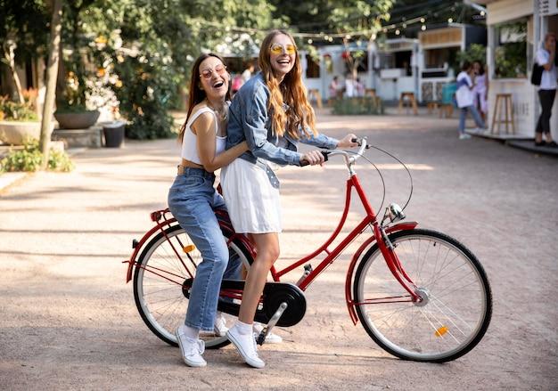 Vue latérale copines à vélo ensemble