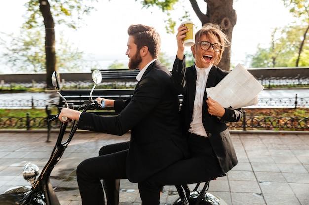Vue latérale d'un couple élégant joyeux monte sur une moto moderne