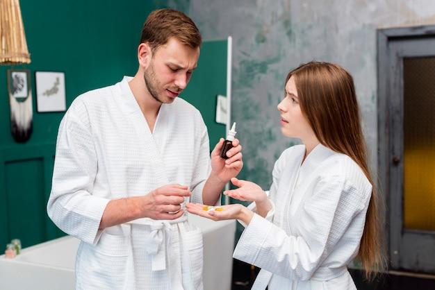 Vue latérale d'un couple en peignoir préoccupé par les pilules
