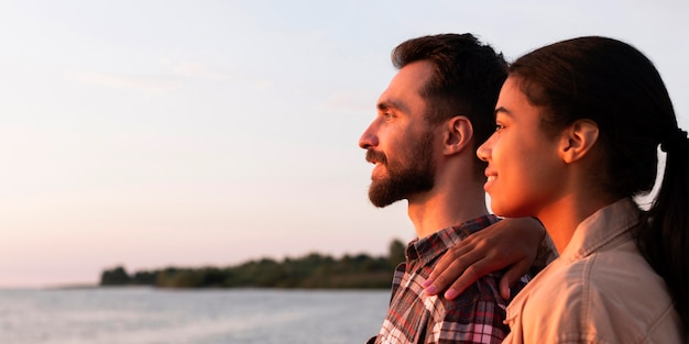Vue latérale couple profitant du coucher de soleil avec espace copie