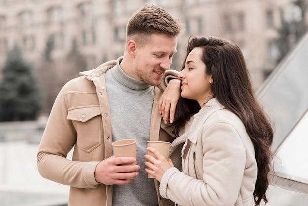 Vue latérale d'un couple romantique à l'extérieur avec des tasses à café