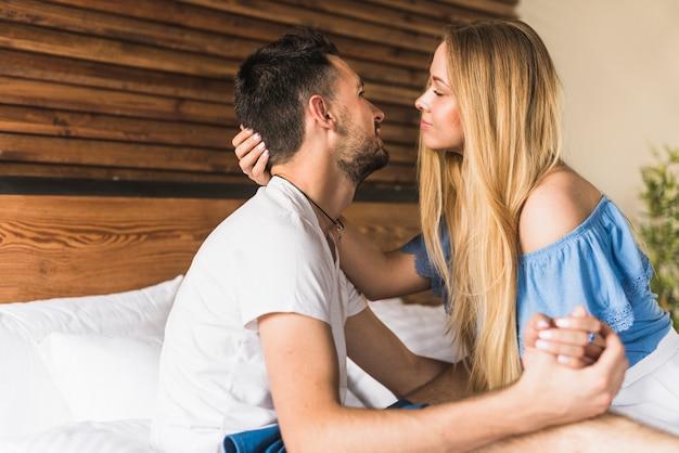 Vue latérale d'un couple romantique sur le lit