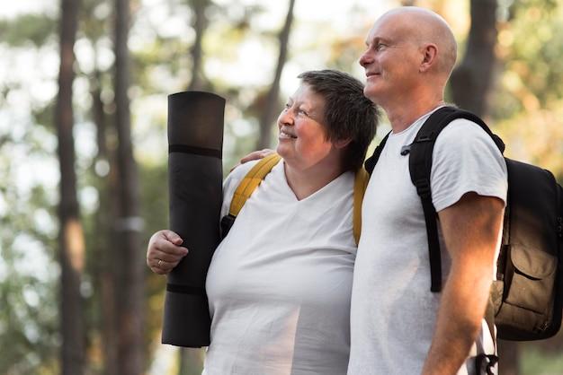 Vue latérale couple avec tapis de yoga
