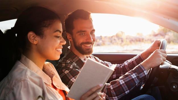 Vue latérale couple voyageant en voiture