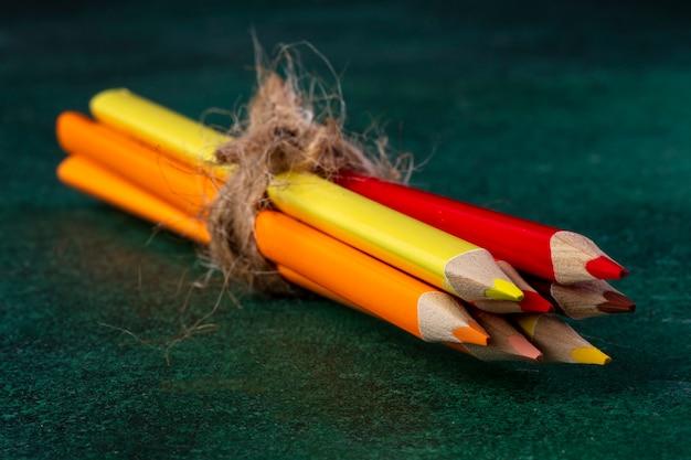 Vue latérale de crayons de couleur attachés avec une corde sur vert foncé