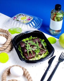 Vue latérale de crêpes noires avec urugula dans une boîte de livraison sur la table