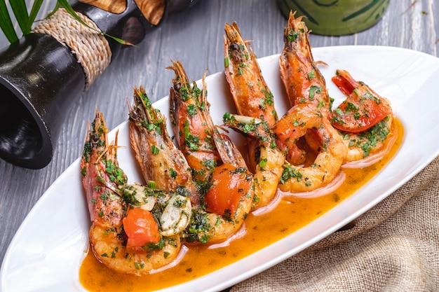 Vue latérale des crevettes frites en sauce avec des tomates et des herbes