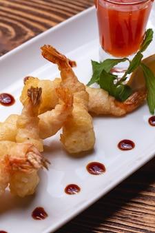 Vue latérale des crevettes en pâte avec sauce