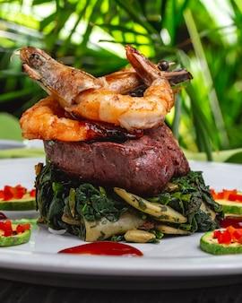 Vue latérale des crevettes royales avec de la viande rouge grillée, des haricots verts et des zukini aux épinards sur une plaque