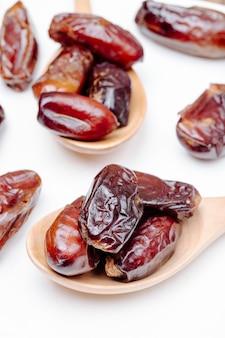 Vue latérale des cuillères en bois avec des dates séchées sur fond blanc