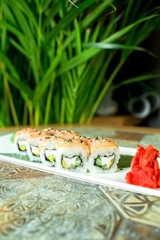 Vue latérale de la cuisine japonaise traditionnelle sushi philadelphia roll avec saumon fromage philadelphia concombre avocat sur vert