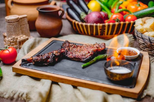 Vue latérale cuisse d'agneau cuisse d'agneau grillée avec des tomates au poivron vert grillées et de la sauce sur un plateau