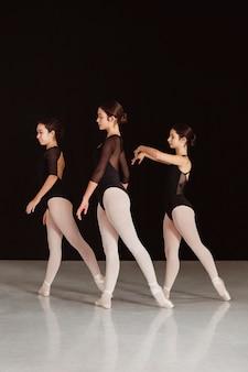 Vue latérale des danseurs de ballet professionnels en justaucorps dansant ensemble