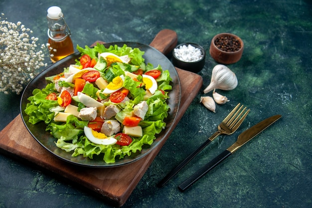Vue latérale d'une délicieuse salade avec de nombreux ingrédients frais sur une planche à découper en bois épices bouteille d'huile ail couverts sur fond de couleurs mélange vert noir