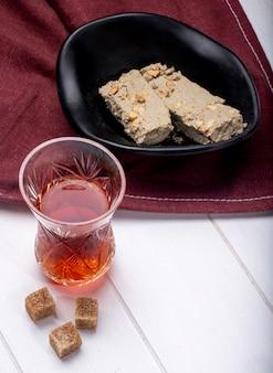 Vue latérale de délicieuses tranches de halva dans un bol noir et un verre de thé armudu sur une nappe