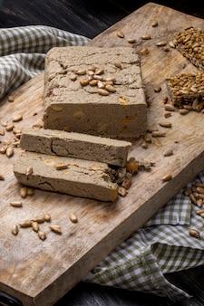 Vue latérale de délicieuses tranches de halva avec des graines de tournesol sur une planche de bois