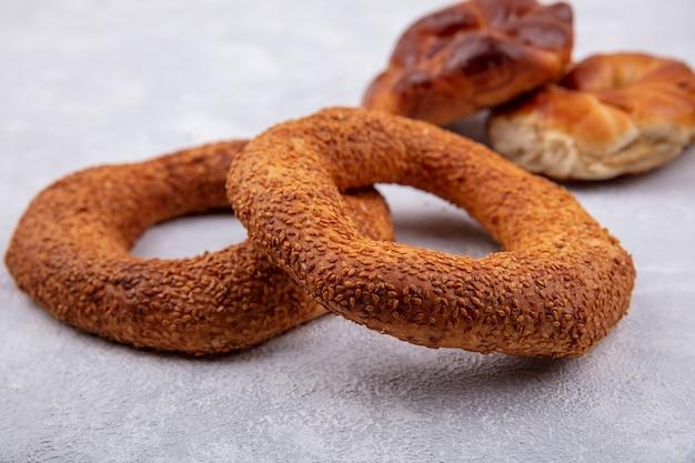 Vue latérale de délicieux et croustillants bagels turcs au sésame sur fond blanc