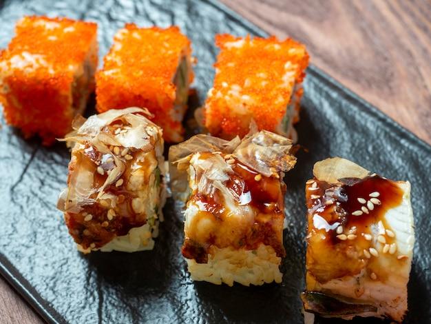 Vue latérale de délicieux petits pains juteux décorés de caviar. cuisine japonaise, plaque noire, gros plan