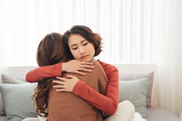 Vue latérale de deux bons amis tristes s'embrassant dans une chambre à l'intérieur d'une maison
