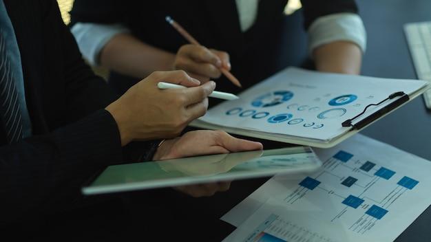 Vue latérale de deux hommes d'affaires consultant sur leur travail avec graphique et tablette