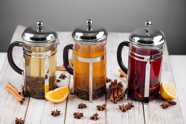 Vue latérale sur différents thés aux fruits dans des pots de presse française