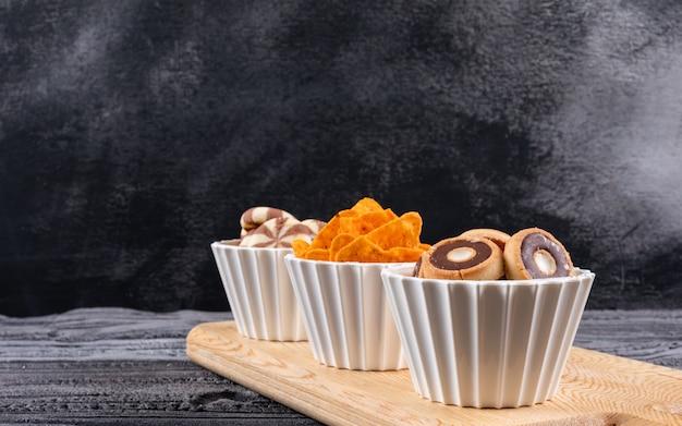 Vue latérale de différents types de collations comme des biscuits et des frites dans des bols sur une planche à découper sur une surface sombre horizontale