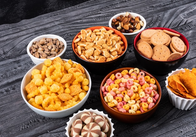 Vue latérale de différents types de collations comme les noix, les craquelins et les biscuits dans des bols sur une surface sombre horizontale