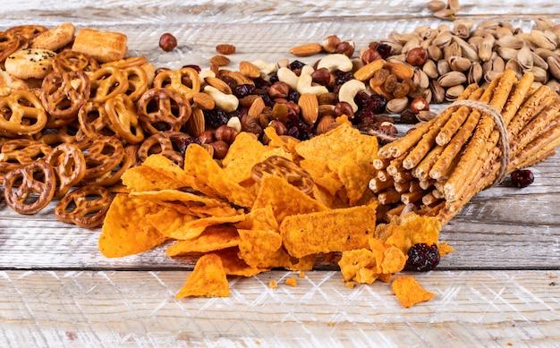 Vue latérale de différents types de collations comme les noix, les craquelins et les biscuits sur une surface en bois blanche horizontale