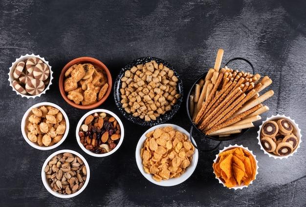 Vue latérale de différents types de collations comme les noix, les craquelins et les cookies dans des bols avec copie espace sur une surface sombre horizontale