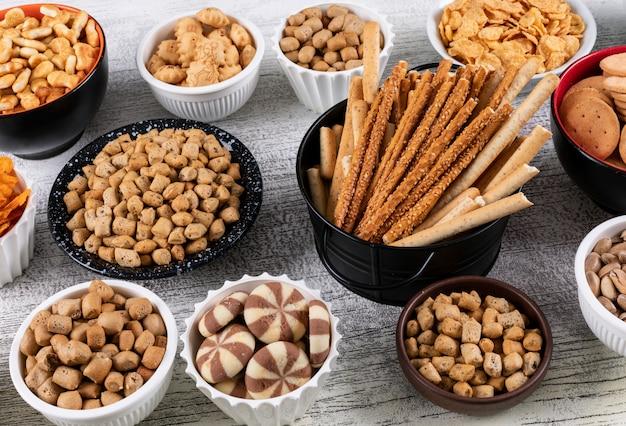 Vue latérale de différents types de collations comme les noix, les craquelins et les cookies dans des bols sur une surface en bois blanche horizontale