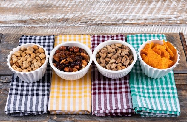 Vue latérale de différents types de collations comme les noix, les craquelins et les cookies sur des serviettes sur une surface en bois blanche horizontale
