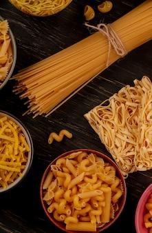 Vue latérale de différents types de macaronis comme tagliatelles de vermicelles de spaghetti et autres sur table en bois